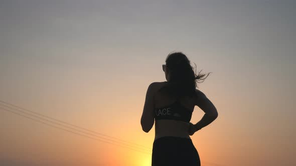 Thumbnail for Active Slim Girl Jogging on Country Road with Evening Sky at Background. Unrecognizable Female