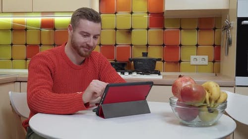 A man watching a video on a tablet while sitting at the kitchen table