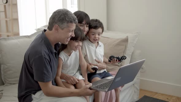 Thumbnail for Cheerful Parents and Two Children with Laptop in Living Room