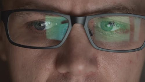 Reflection Of Scrolling Sites In An Eyeglasses Of Young Adult Man In A Dark Room