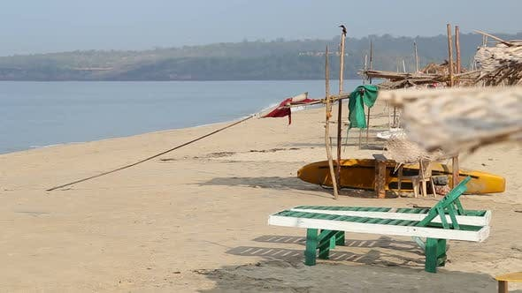 Thumbnail for Deck chairs and boat at empty sandy beach in Goa.
