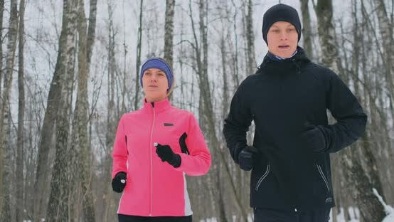 Thumbnail for Positive Beautiful Young Healthy Couple Running with Sportswear Through the Forest in the Sunny