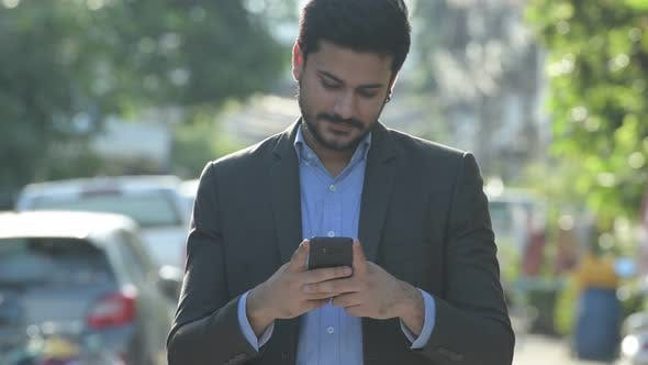 Thumbnail for Young Happy Bearded Indian Businessman Using Phone Outdoors