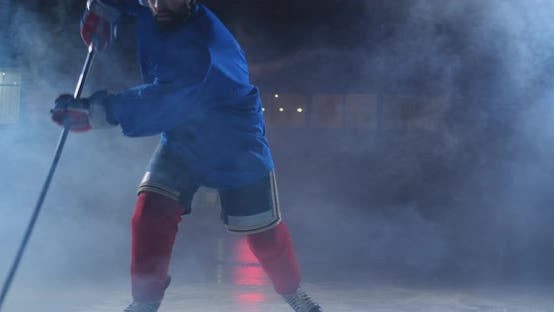 Cover Image for Professional Hockey Player with a Stick and a Puck Moves on Luda in Skates and Helmet