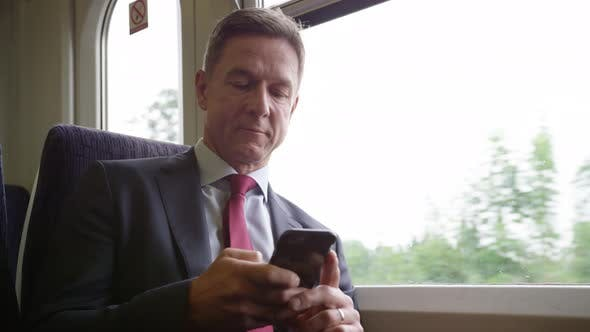 Commuter on his way to work looking at smart phone