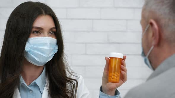 Female Doctor Prescribing Medication Pills To Senior Male Patient Indoors