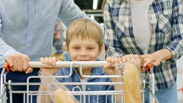Thumbnail for Boy Pushing Shopping Cart and Running with Parents in Supermarket