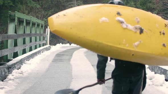 Thumbnail for Extreme Athlete Carries Whitewater Kayak Over Bridge In Winter Snow