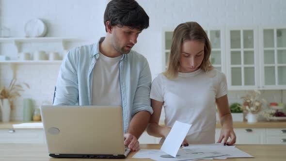 Thumbnail for Young Family Having Debt Problems. Female and Man Studying Paper Form Bank While Managing Domestic