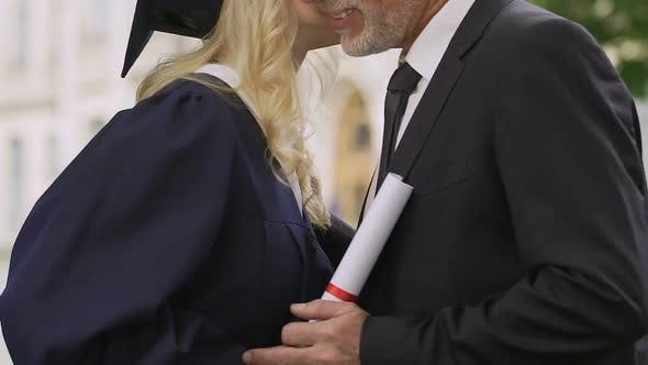 Thumbnail for Cheerful female student  kissing father at graduation ceremony, family support
