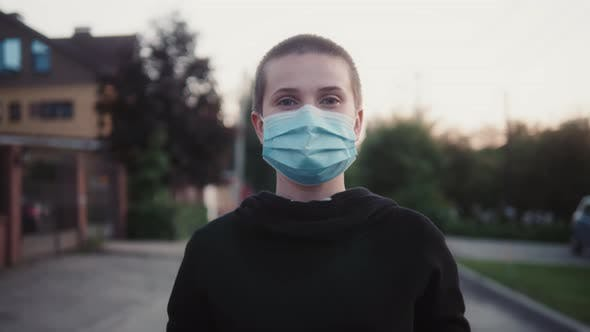 Short Haired Young Bald Adult Woman Wearing Protective Facial Mask on Face on Street