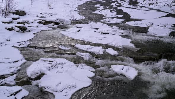 Thumbnail for Mountain Stream in Winter. Mountain River Flowing Over Ice and Snow Near Rocks in Winter Landscape