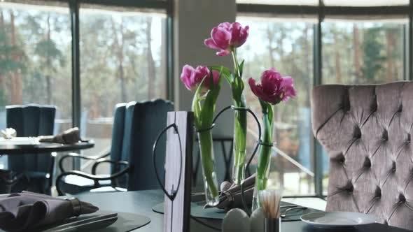 Thumbnail for Teller mit Serviette und Besteck zum Abendessen im Restaurant. Blumen auf Esstisch