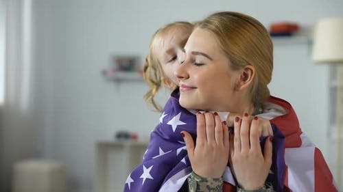 Little Daughter Covering Soldier Mother With US Flag, Happy With Homecoming