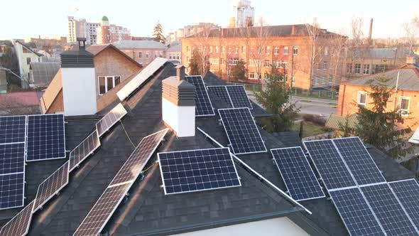 Aerial shot of modules or photovoltaic solar panels along a roof for renewable energy