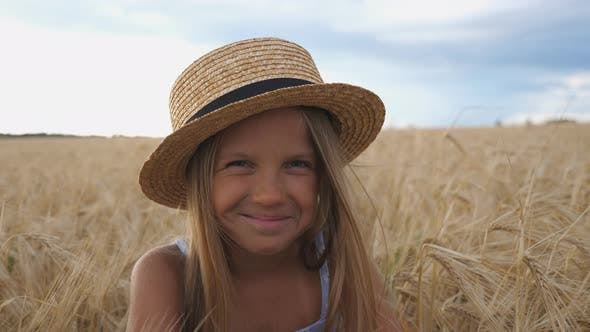 Thumbnail for Close Up of Beautiful Smiling Girl in Straw Hat Looking Into Camera Against the Background of Barley