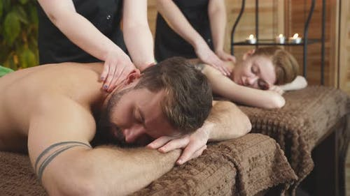 Young Couple Receiving Back Massage at Beauty Spa