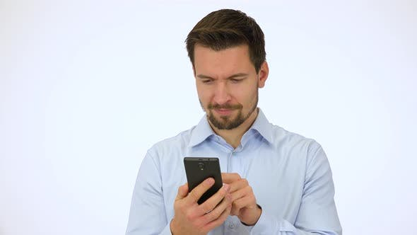 Thumbnail for A Young Handsome Man Works on a Smartphone, Then Smiles at the Camera - White Screen Studio