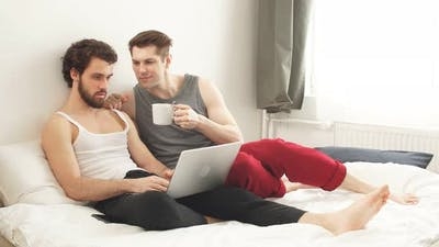 Happy Gay Couple Using Tablet in Bed. Gay Couple