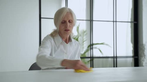 Mature Woman Wipes a Wooden Table with a Rag