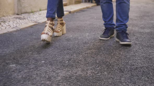 Thumbnail for Legs of Young Man and Woman Walking on Street
