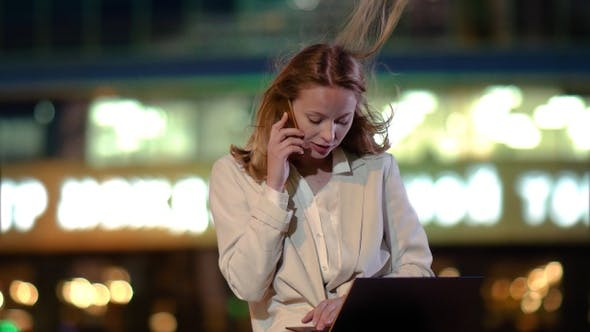 Thumbnail for Girl making a business call on cellphone while typing something