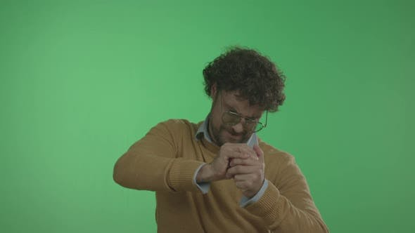 Casual Man Squeezes Juice From Apple with His Hands.