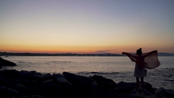 Silhouette of Slim Woman Dancing with Scarf on the Beach at Sunset