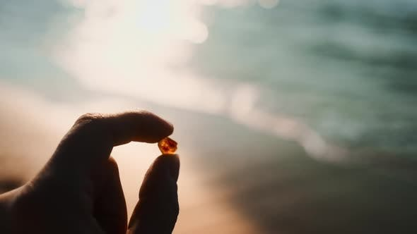 Shot of Woman's Hand Holding A Beautiful Amber Towards The Coast
