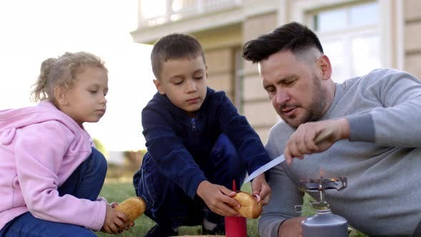 Caucasian Father Making Hotdogs with Kids on Gas Cooker