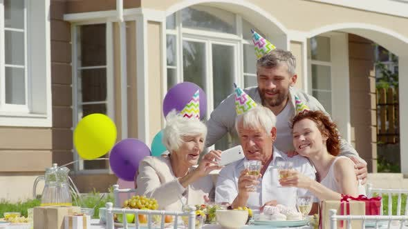 Thumbnail for Happy Family in Party Hats Taking Selfie on Outdoor Birthday Dinner