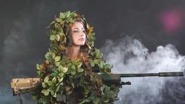 Thumbnail for Camouflaged Woman Sniper in Ghillie Suit Posing with Rifle in Foggy Night. Slow Motion