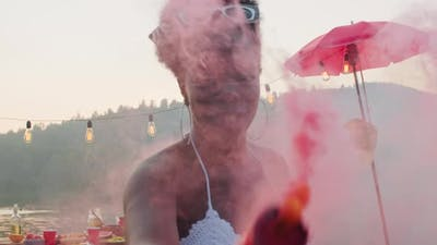 Happy Black Woman Dancing with Colored Smoke Bomb at Summer Party