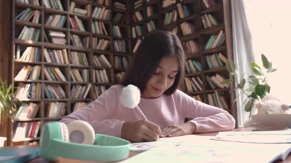 Cute Indian Latin Preteen School Girl Pupil Studying at Home Sitting at Desk