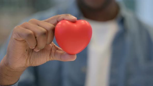 Close Up of African Man Holding Heart Shape Object