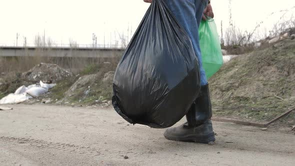 Male Legs in Boots Walking at Garbage Dump