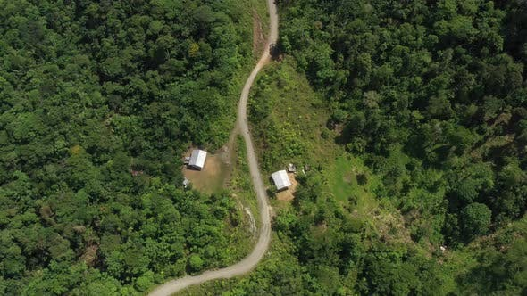 Thumbnail for Two houses with tin roofs along a dirt road and surrounded by tropical forest