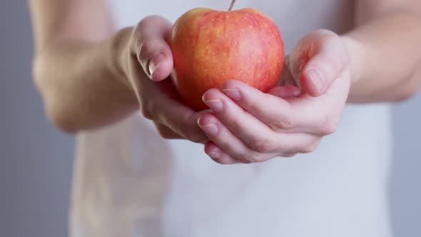 Thumbnail for Closeup Image of a Woman Holding and Giving a Red Apple