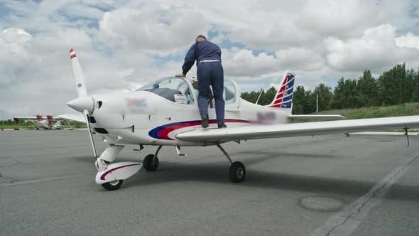 Mature Pilot Getting into Plane