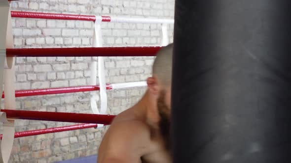Bearded Professional Male Boxer Training with Punching Bag