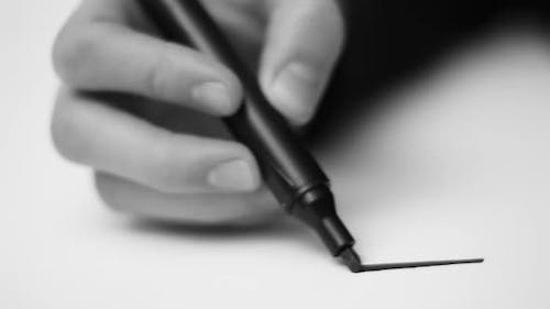 An artist draws with a felt tip pen marker on a white board.