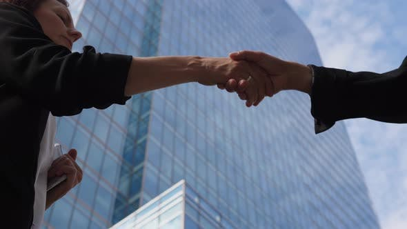 Close Up of Female Handshake in Front of Skyscrapers