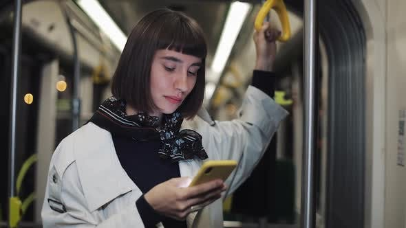 Thumbnail for Portrait of Young Hipster Woman Holds the Handrail Using Smartphone Standing in Public Transport