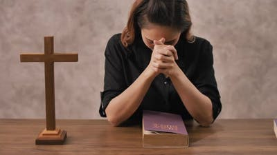 A young Asian Christian woman praying to Jesus Christ in a church.