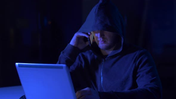 Hacker with Laptop Calling on Cellphone