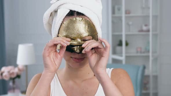 Cover Image for Young Caucasian Woman Removing Rejuvenating Cosmetic Golden Tissue Mask on Face