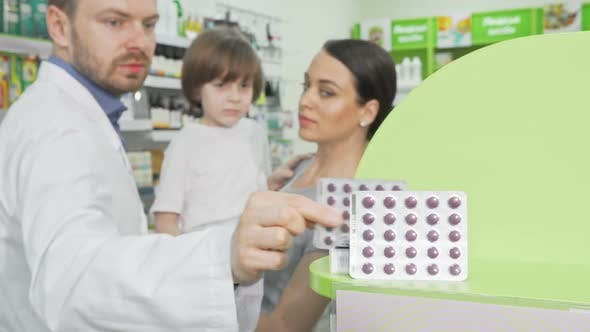Cover Image for Pharmacist Giving Blister with Pills To a Little Boy and His Mother