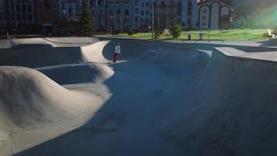 Skateboarder Practicing in Bowl Ramp in the Morning