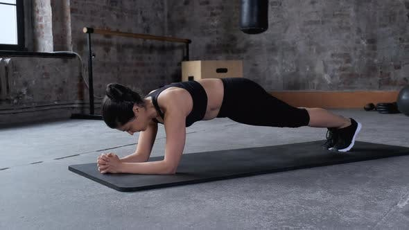 Young pretty woman doing plank the gym, Concept of sport and healthy lifestyle