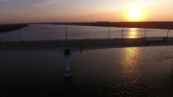 Thumbnail for Aerial Shot of Big Bridge Covering the Dnipro at Shimmering Sunset in Summer